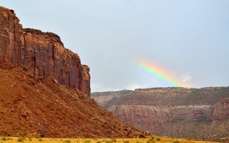 A landscape with a desert valley, with rocks in the foreground and a faint rainbow in the background