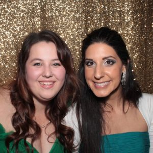 Brittany and Amy are elegantly dressed up for a holiday party. Brittany's hair is curled and Amy is wearing sparkly earrings. They are standing in front of a gold curtain.