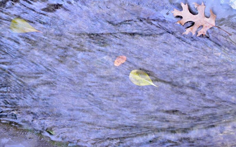 Water flowing in a stream with a floating leaf in the top right corner