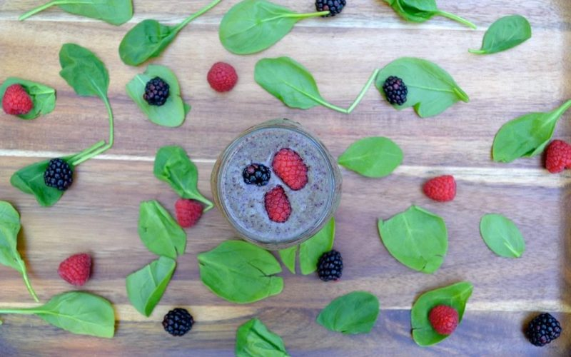 Aerial picture of a purple smoothie on a cutting board. Baby spinach leaves, raspberries and blackberries are placed decoratively around it