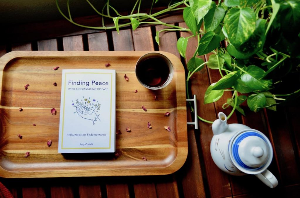 Amy's book is on a wooden tray along with a cup of tea. On the right of the tray, there is a teapot and a green plant