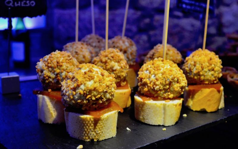 Delicious looking tapas on a counter. There are 10 of the same tapa, which is a cheese ball covered in crushed nuts and a piece of ham on a small round toast, held together with a toothpick