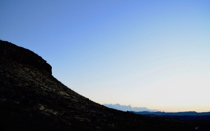A blue sky with the silhouette of a mountain in the forefront